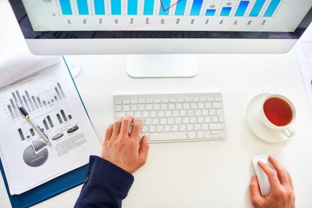 Człowiek siedzący przy komputerze z dokumentami z wykresami