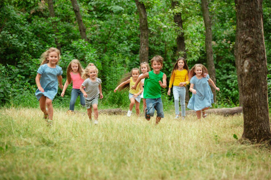 Grupa dzieci biegnąca po łące